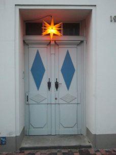 Eingangstür mit Rauten-Kassetten. beleuchteter Weihnachtsstern.